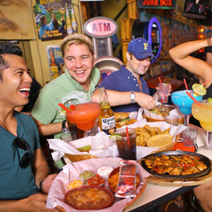 Four friends enjoying various food and Mega Margaritas