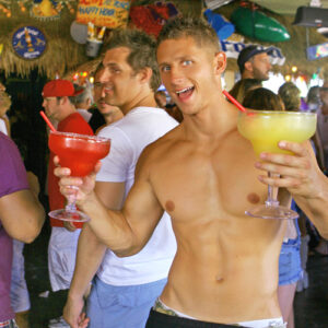 Fiesta Cantina server with 2 Mega Margaritas, guests in background